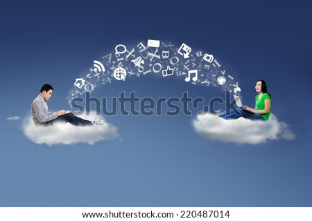 Two people sitting on cloud using laptop to share information - stock photo