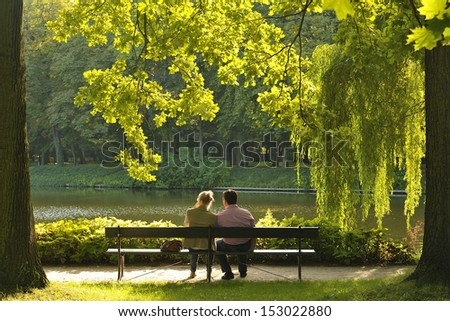 Two people sitting on the bench in the park - stock photo