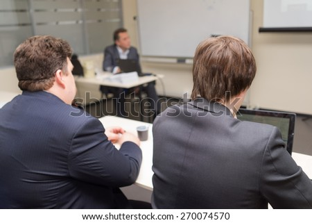 two people sitting rear and watching the conference - stock photo