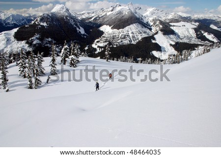 Two people snowshoeing in the winter season on the snow mountain peak near BC, Canada. - stock photo