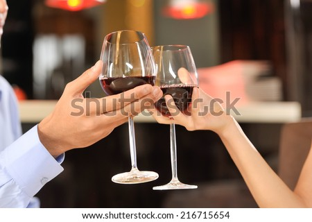 Two people toasting with wine glasses. young couple drinking red wine at bar - stock photo