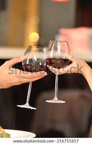 Two people toasting with wine glasses. young couple drinking red wine at restaurant