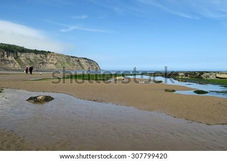 Two people walk on Robin Hood Bay deserted beach. Robin Hood Bay, North Yorkshire, UK. - stock photo