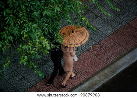 Two people walking in the rain sheltering under a bamboo Umbrella on the streets of Saigon(Ho Chi Min City), Vietnam - stock photo