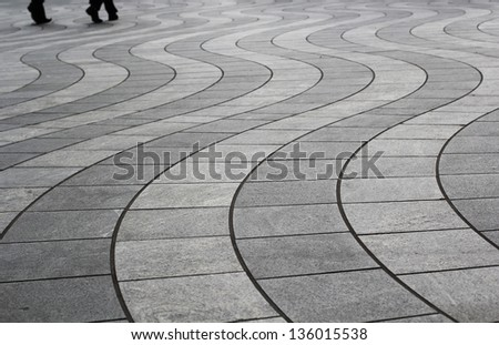 Two people walking on a beautiful Wavy Tile Patterns in Canary Wharf, London - stock photo