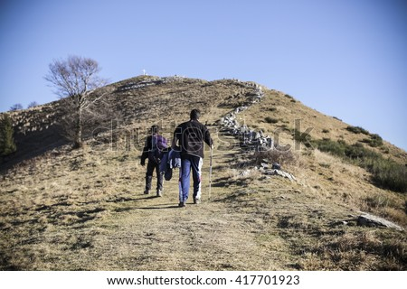 Two people walking on a mountains landscape