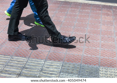 two people walking on the sidewalk - stock photo
