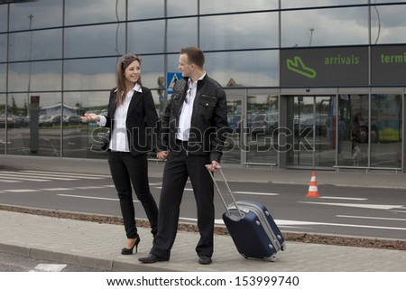 Two people with suitcase at the airport parking