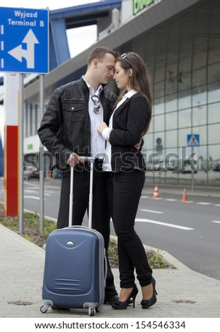 Two people with suitcase at the airport parking. Poland - stock photo