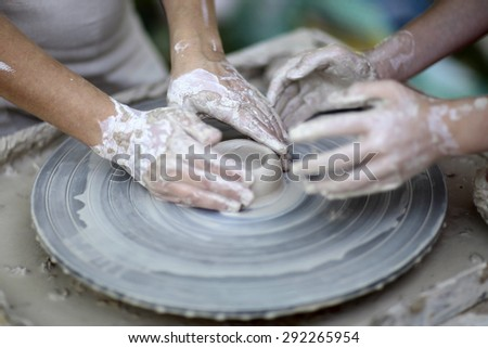 Two people working hands with white grey clay on a potter's wheel outdoor closeup, horizontal picture