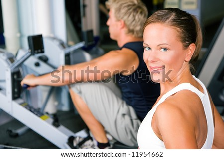 Two people working out in a gym using a rowing machine