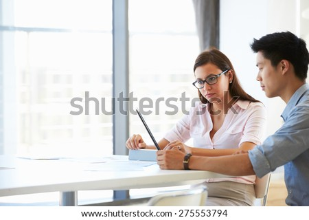 Two people working with digital tablet in empty meeting room - stock photo