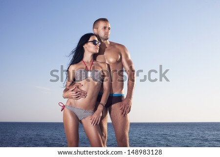 Two perfect bodies person posing on sea background. Male and female. - stock photo