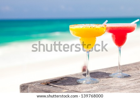 two perfect mango and strawberry margarita, beach background - stock photo