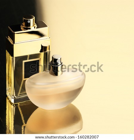 Two perfume bottles on gold background with reflection.