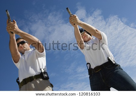 Two persons aiming target with handgun, low angle view