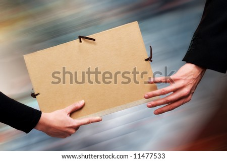 Two persons exchanging a file as a relay baton. Motion blur at the background. - stock photo