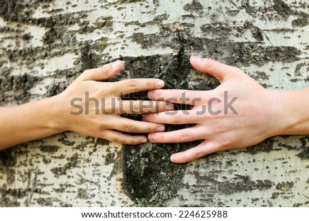 Two persons hugging trunk large tree, close-up - stock photo