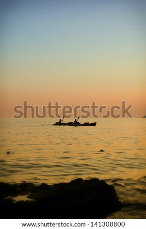 Two persons in kayaks on the sea at sunset as symbol of balance in life - stock photo