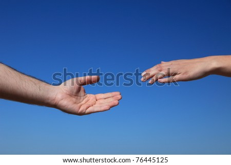 Two persons trying to reach hands. All in front of bright blue sky.