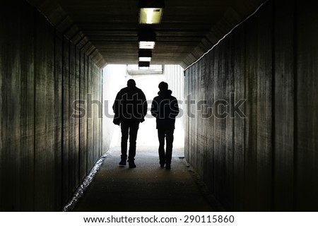 Two persons walk to the light in the end of the tunnel. - stock photo