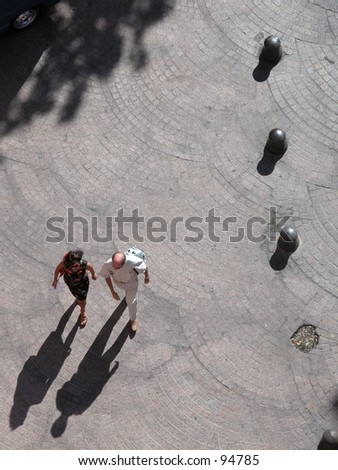 Two persons walking in the street, seen from a high standpoint - stock photo