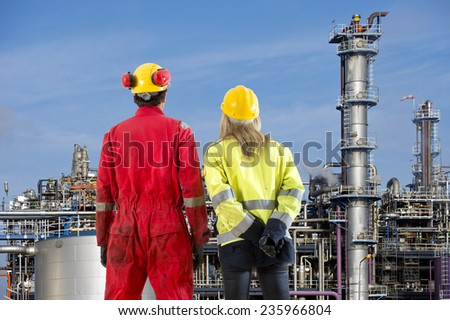 Two petrochemical engineers looking at a new cracking facility for hydrocarbon products used in polyurethane compounds - stock photo