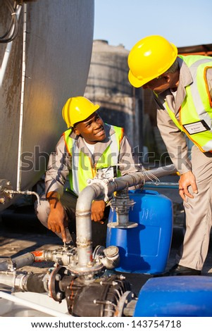 two petrochemical workers inspecting pressure valves on a fuel tank - stock photo