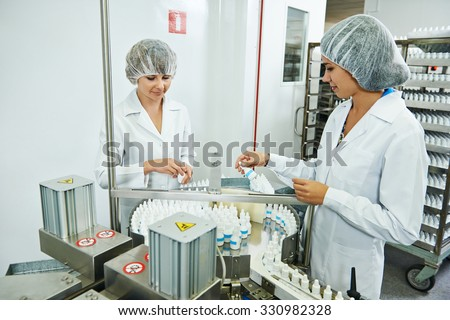 Two pharmaceutical factory workers at pharmacy industry manufacture checking medicine on conveyer  - stock photo