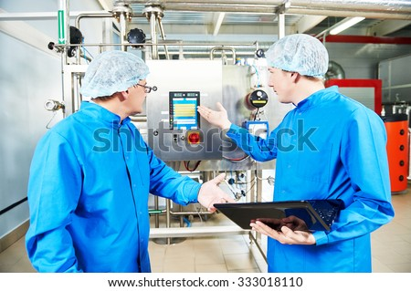 Two pharmaceutical male workers operating air conditioning equipment at pharmacy industry manufacture factory using notebook computer - stock photo