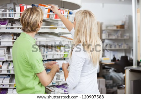 Two pharmacists filling drug prescription - stock photo