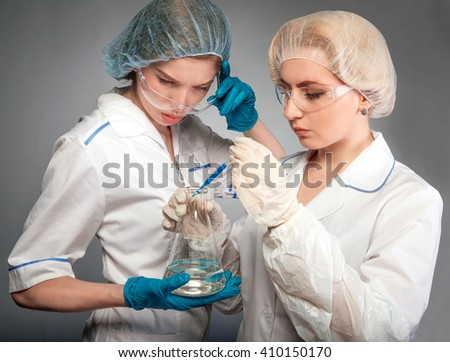 Two pharmacists in the lab to conduct experiments, chemical analysis. One woman chemist adds reagent into the flask, and the second doctor looks at the result with surprise. - stock photo