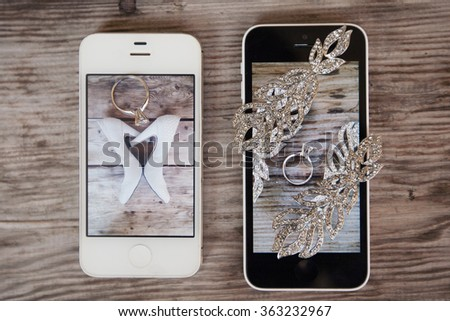 two phones with wedding rings