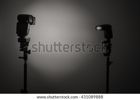 Two Photo camera flash speedlights with honeycombs on stands strobes. Black and white - stock photo