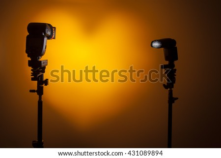 Two Photo camera flash speedlights with honeycombs on stands strobes. Draw heart symbol with lighting. Studio. Orange background - stock photo
