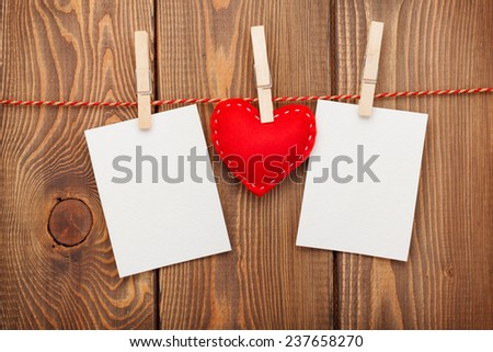 Two photo frames and valentines day toy heart over wooden background - stock photo