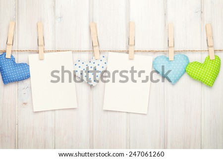 Two photo frames and valentines day toy hearts over white wooden background - stock photo