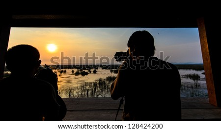 Two photographer taking sunset photo with wooden window frame - stock photo