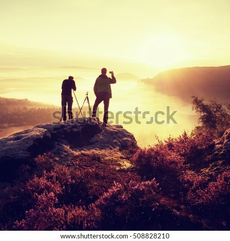 Two photographers on cliff takes sunrise photos. Dreamy fogy landscape, orange mist in a beautiful valley below