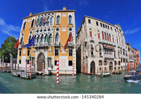 Two picturesque Venetian palace, separated by a narrow channel. The facade of the palace is decorated with colorful flags fluttering in the wind. Photo taken by lens Fisheye - stock photo