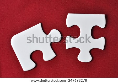 Two Pieces Jigsaw Puzzle On the Red Background - stock photo