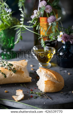 Two pieces of baguette with herbs and seasoning, rustic dark style photo, closeup shot, selective focus - stock photo