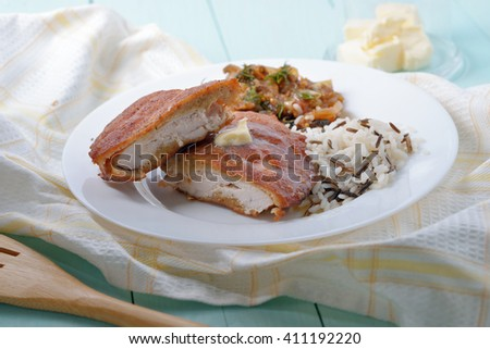 Two pieces of battered chicken fillet with rice and mushrooms as a garnish. - stock photo