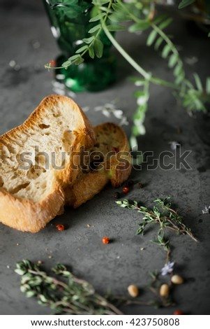 Two pieces of bread with herbs and seasoning, rustic dark style photo, closeup shot, selective focus - stock photo