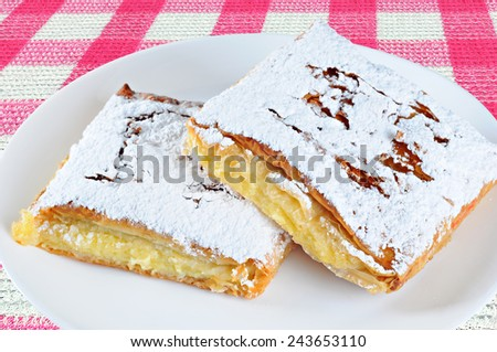 Two pieces of cheese pie with sugar on a plate, on a tablecloth  - stock photo