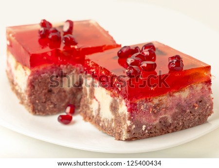 Two pieces of cheesecake on a plate with pomegranate seeds - stock photo