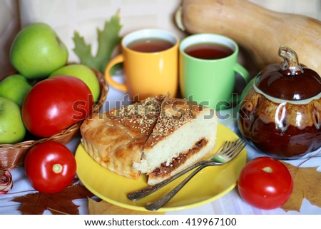 Two pieces of fresh baked cabbage pie (tart, pasty, cake, calzone, kulebyaka) on the yellow plate serving with red tomatoes, green apples, pumpkin, tea, foliage and vintage forks, selective focus - stock photo