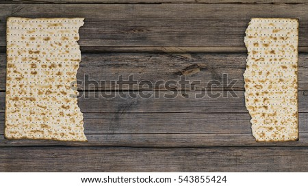 Two pieces of matzah or matza on a vintage wood background with copy space or text space. Perfect for your Passover design.