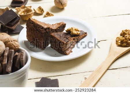 two pieces of nut cake and ingredients on aged wooden table