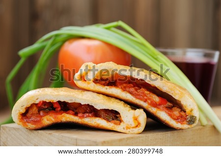 Two pieces of pizza calzone with glass of red wine, fresh scallion and tomato on wooden board - stock photo